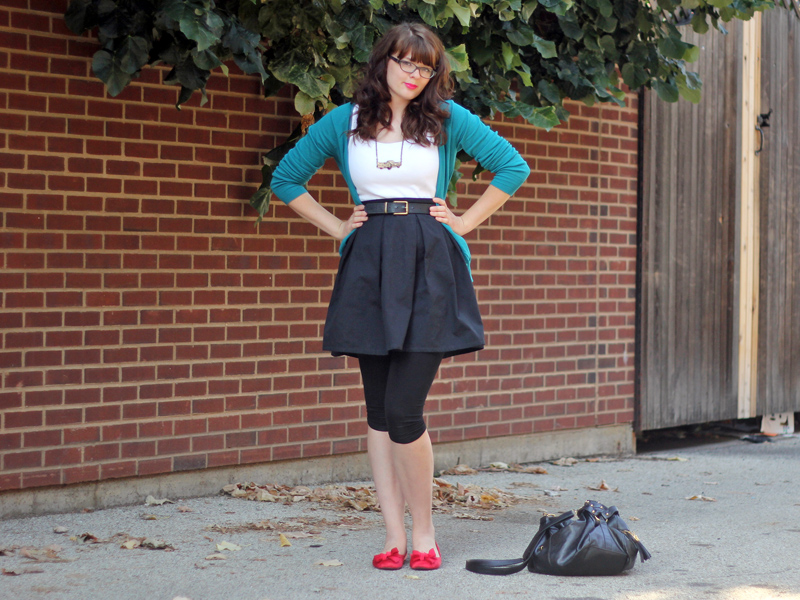 Green cardigan, black belted skirt, leggings, and red flats